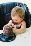 messy baby eating chocolate cake