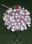 purple candy sundae centerpiece in ice cream glass with straw and red candy for the cherry