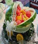 watermelon baby carriage centerpiece with assorted fruit and white sheer ribbon