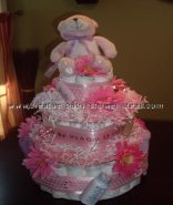 pink daisy polka dot diaper cake with pink and white paper shred