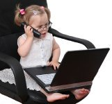 busy little girl with cell phone and laptop sitting in business chair