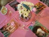 closeup of pink table at a baby shower with large alice and wonderland pictures as placeholders and white flowers in the center