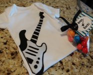 white baby onesie with black and white appliqued guitar
