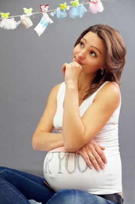 pregnant woman thinking while looking at baby clothesline