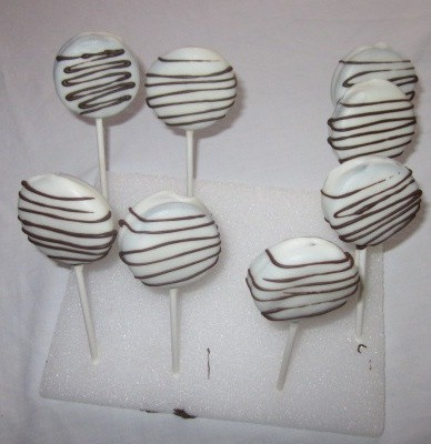 white chocolate covered oreo lollipops standing up to dry