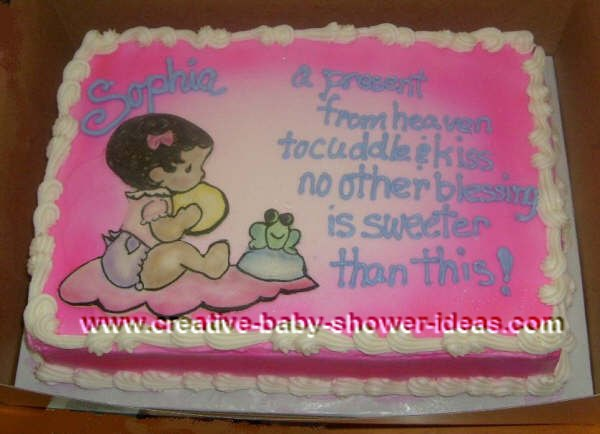 pink baby shower cake with picture of baby sitting on a blanket next to a smiling frog