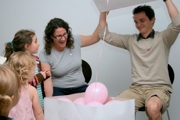 happy mom and dad at gender reveal opening box and seeing pink balloons