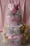 girl diaper cake wrapped with pink and white receiving blankets with silver mesh ribbon