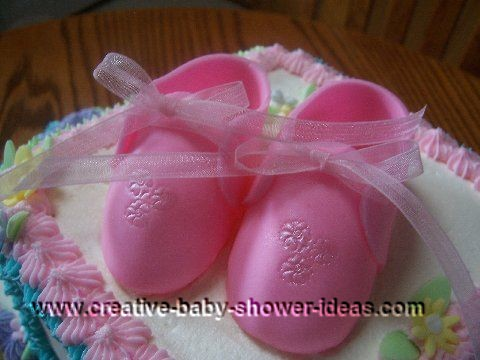 closeup of pink booties on blocks cake