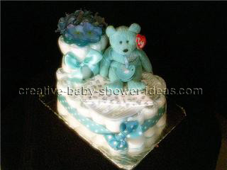 baby bootie cake with blue and white polka dot ribbon and teddy bear