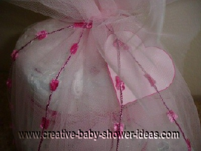 diaper cake tied with white tulle and a pink heart card