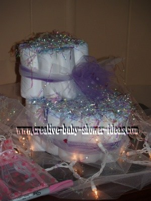 purple and white baby bootie diaper cake on table