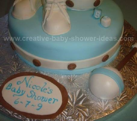closeup of blue and white baby bootie cake with rattle
