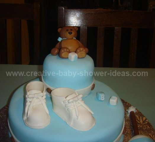 closeup of brown bear on top of baby bootie cake