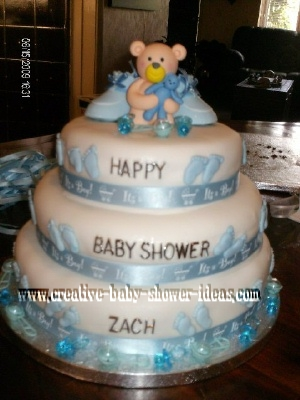 white fondant baby bootie cake with blue footprints