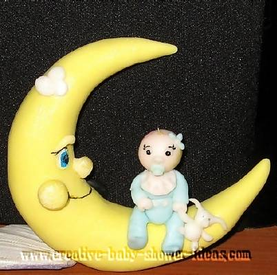 top of moon baby cake with baby wearing blue sleeper sitting on top