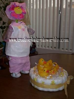 sunflower doll diaper cake standing on doll stand next to 1 tier duck diaper cake