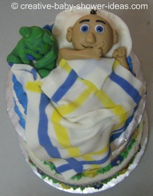 sleeping baby cake with baby sucking thumb next to green bear
