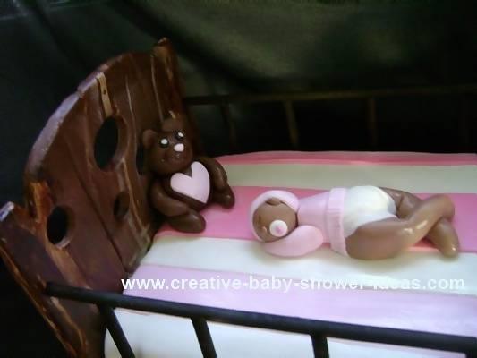 close up of baby sleeping in baby shower crib cake