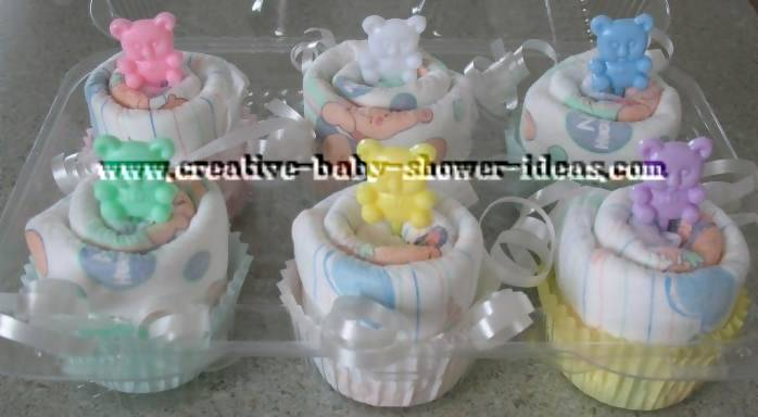 6 baby diaper cupcakes with colorful bear picks in a cupcake tray