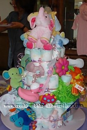 colorful pink and green baby diaper cake with elephant on top