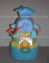 back of elephant diaper cake with blue and green blankets surrounding layers and yellow ducky toy sticking out