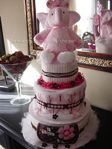pink and brown elephant diaper cake with modern pink and brown baby blankets covering the layers