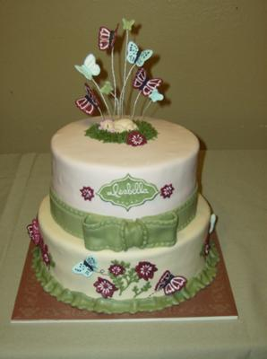 white cake with green bow and purple flowers