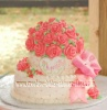 white cake covered with pink roses