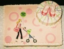 sheet cake with mod mom pushing stroller design and baby booties on 2 tier