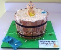 smiling baby in a barrell bathtub cake with white bubbles and baby toys