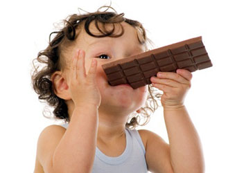 baby with curly hair eating candy bar