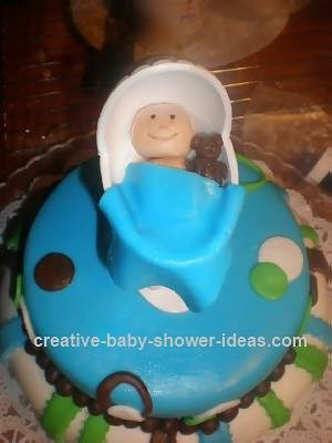 top of baby shower carriage cake with smiling baby