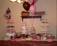 mod mom baby shower dessert table with pinks and browns and a diaper cake