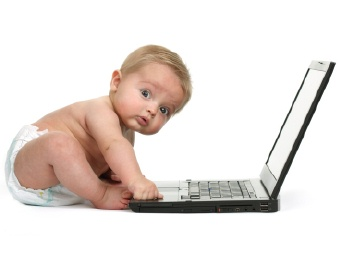 baby typing on computer and looking at camera