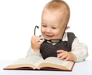smiling baby holding glasses and looking at book