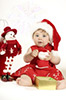 cute baby dressed in santa dress holding present