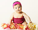 baby in pink sun dress and headband, surrrounded by hawaiian flowers