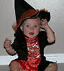 cute baby girl in black and orange witches outfit and hat