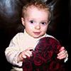 cute baby boy in cream sweater holding onto a red valentine heart box