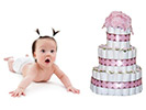 cute surprised baby with pig tails next to pretty diaper cake