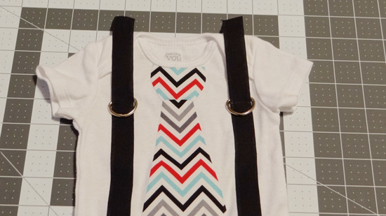 baby onesie showing placement of D rings on suspenders