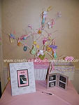 pink table with signed picture of baby sonogram and a white painted tree with baby items tied to it