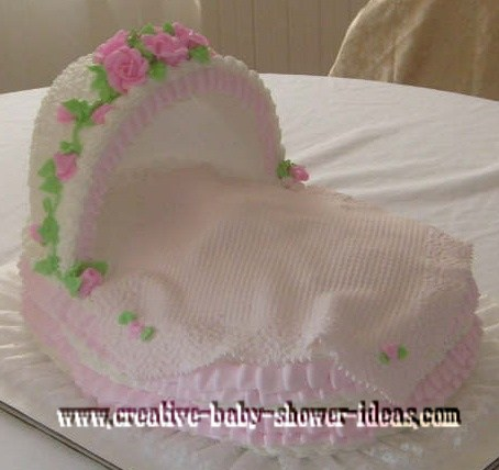 pink and white bassinet cake with flowers and blanket