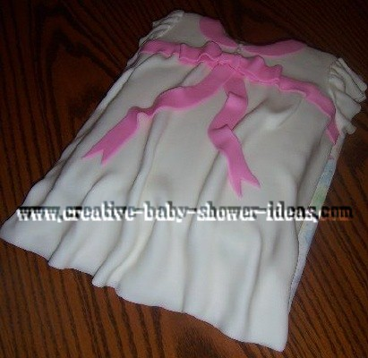 white baby shower dress cake with pink bow