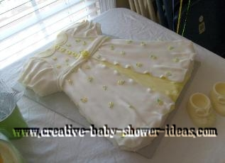 white and yellow baby dress cake