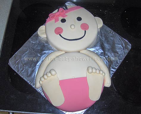 smiling baby girl cake with pink fondant diaper and headband
