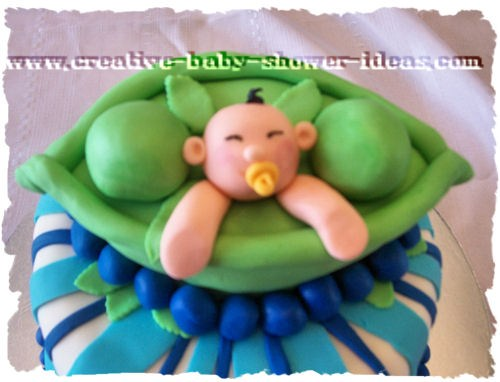 closeup of peas in a pod cake with baby face and arms peeking out