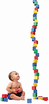 smart baby looking at a tall stack of blocks