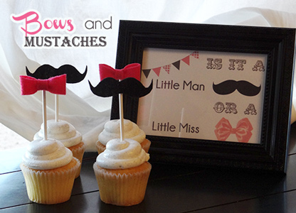 white cupcakes with pink bows and mustache lollipop decorations